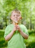 Giovane ragazzo che mangia un gelato saporito esterno Fotografia Stock Libera da Diritti