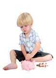 Giovane ragazzo che mette soldi in una banca piggy Immagine Stock