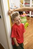 Giovane ragazzo che ottiene misura di altezza in porta Immagine Stock