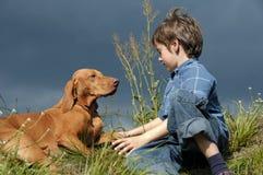 Giovane ragazzo che parla con suo cane Immagine Stock