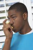 Giovane ragazzo che per mezzo dell'inalatore di asma Fotografie Stock Libere da Diritti
