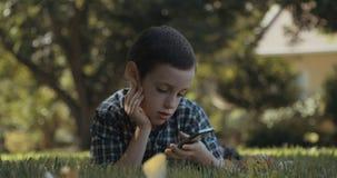 Giovane ragazzo che per mezzo di un telefono cellulare all'aperto sull'erba video d archivio