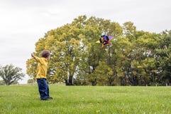 Giovane ragazzo che pilota un aquilone Immagini Stock