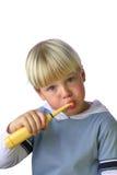 Giovane ragazzo che pulisce i suoi denti fotografia stock