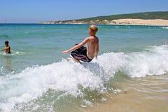 Giovane ragazzo che salta nell'onda su una spiaggia piena di sole fotografia stock libera da diritti
