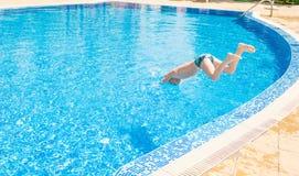 Giovane ragazzo che salta nella piscina Fotografia Stock