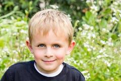 Giovane ragazzo che si siede nel giardino Fotografie Stock