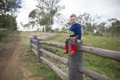 Giovane ragazzo che si siede su una posta e su un recinto di ferrovia stagionati su un'azienda agricola in Toowoomba Fotografie Stock Libere da Diritti