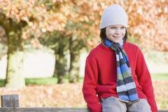 Giovane ragazzo che si siede sulla rete fissa Immagini Stock Libere da Diritti
