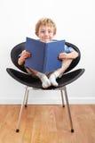 Giovane ragazzo che si siede in una presidenza che legge un libro fotografie stock libere da diritti