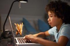 Giovane ragazzo che studia allo scrittorio in camera da letto nella sera sul computer portatile Fotografie Stock Libere da Diritti