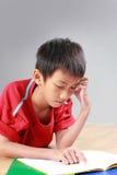 Giovane ragazzo che studia sul pavimento Fotografie Stock