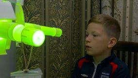 Giovane ragazzo che subisce trattamento in clinica moderna inalazione del laser trattamento leggero di inalazione della gola UV immagini stock