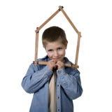 Giovane ragazzo che tiene nastro di misurazione casa-a forma di Immagini Stock Libere da Diritti