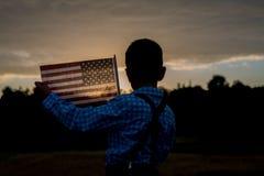 Giovane ragazzo che tiene una bandiera americana, riconoscente per libertà Immagini Stock