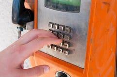 Giovane ragazzo che tocca un vecchio telefono pubblico arancio inutilizzato e unfunctional fotografia stock libera da diritti