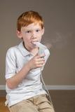 Giovane ragazzo con asma che completa un trattamento respirante Fotografie Stock