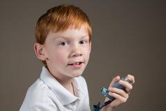 Giovane ragazzo con asma che tiene un inalatore Immagini Stock