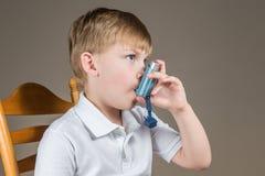 Giovane ragazzo con asma facendo uso di un inalatore blu Fotografia Stock Libera da Diritti