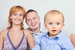 Giovane ragazzo con i suoi genitori nei precedenti immagine stock