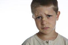 Giovane ragazzo con i sussidi di fascia sul fronte Fotografie Stock