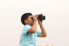 Giovane ragazzo con il binocolo. fotografia stock libera da diritti