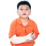 Giovane ragazzo con il braccio rotto nel getto di intonaco fotografia stock