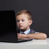 Giovane ragazzo con il computer bambino divertente che guarda in taccuino Fotografie Stock Libere da Diritti