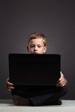 Giovane ragazzo con il computer bambino divertente che guarda in taccuino Immagine Stock