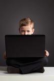 Giovane ragazzo con il computer bambino divertente che guarda in taccuino Fotografia Stock
