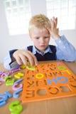 Giovane ragazzo con il puzzle delle lettere Immagine Stock Libera da Diritti