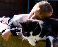 Giovane ragazzo con il sonno del gatto Immagine Stock
