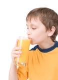 Giovane ragazzo con il succo di arancia fotografia stock