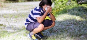 Giovane ragazzo con l'allergia del polline con il fazzoletto Fotografie Stock