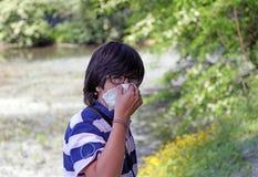 Giovane ragazzo con l'allergia del polline con il fazzoletto bianco Immagini Stock