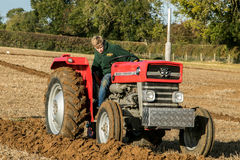 Giovane ragazzo con l'aratura rossa d'annata del trattore Fotografie Stock Libere da Diritti