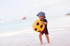 Giovane ragazzo con la sfera gialla sulla spiaggia immagini stock
