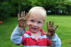 Giovane ragazzo con le mani fangose Fotografie Stock Libere da Diritti