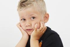 Giovane ragazzo con le mani sul mento fotografia stock