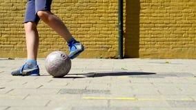 Giovane ragazzo con una palla su un passo di calcio della via archivi video