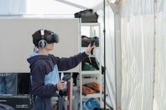 Giovane ragazzo con VR - i vetri ed i regolatori gioca il gioco Fotografie Stock Libere da Diritti