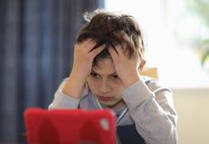 Giovane ragazzo confuso che esamina compressa Immagine Stock Libera da Diritti