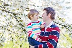 Giovane ragazzo del bambino e del padre in giardino di fioritura Fotografia Stock