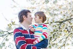 Giovane ragazzo del bambino e del padre in giardino di fioritura Fotografie Stock Libere da Diritti