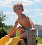 Giovane ragazzo del bambino incerto di scendere uno scorrevole della piscina Fotografia Stock