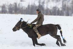 Giovane ragazzo del Tuva che fa concorrenza in una concorrenza dell'ippica nelle montagne di Altai in Cina Fotografia Stock