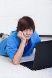 Giovane ragazzo dell'adolescente con il computer portatile Fotografie Stock