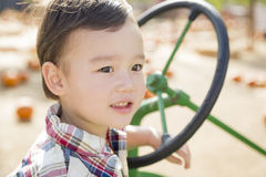 Giovane ragazzo della corsa mista che gioca sul trattore Immagine Stock