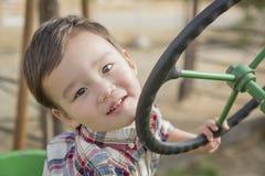 Giovane ragazzo della corsa mista che gioca sul trattore Immagini Stock Libere da Diritti