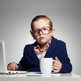Giovane ragazzo di affari bambino in vetri piccolo capo in ufficio Immagine Stock